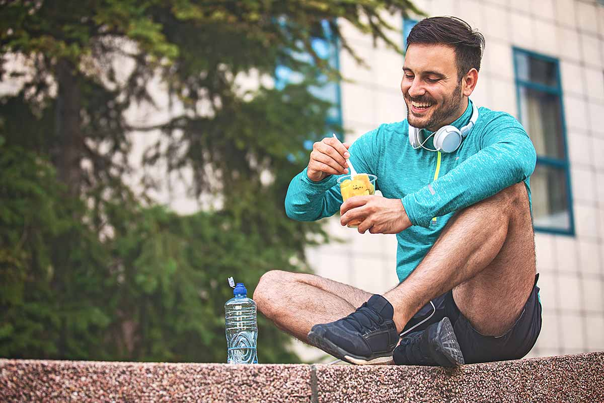 Young athlete man eating fruit post-exercise.