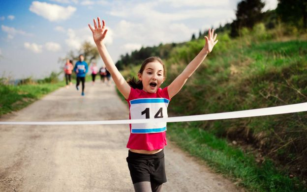 young female athlete running through finish line