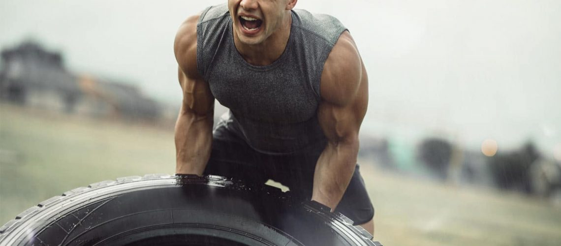 Strong athlete doing a tire flip exercise