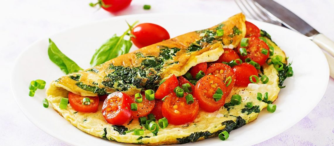 Omelette with tomatoes, spinach and green onion on white plate.  Frittata - italian omelet.