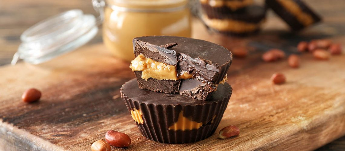 Tasty chocolate peanut butter cups on wooden board
